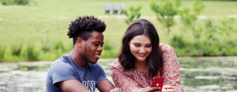 Students on a bench at the lake looking at a phone