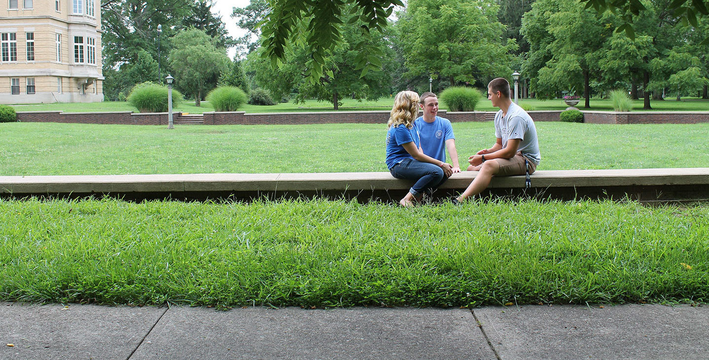 Students sitting along the side of the Sunken Garden