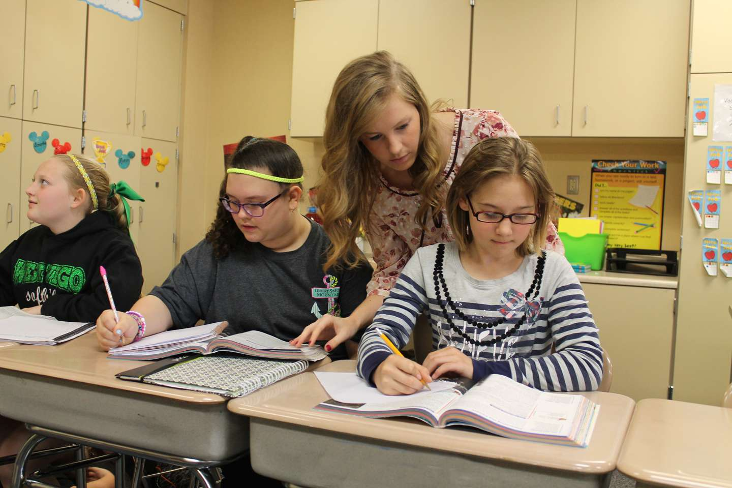 Education student helping elementary students