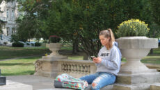 Student on phone in front of Guerin Hall