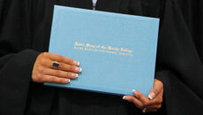 Student holding diploma at commencement