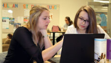 Student helping another using a laptop