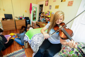 Girl playing violin in dorm room