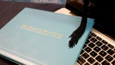 Diploma and tassel sitting on laptop