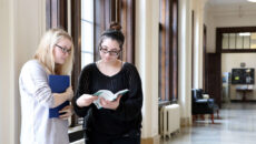 Two students standing in the lobby of Le Fer Hall reading a book