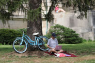 Student studying under a tree with a bicycle beside her