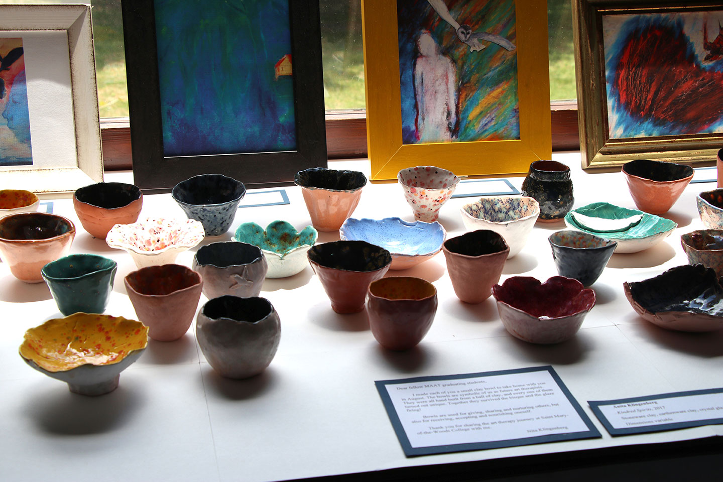 art exhibit with paintings and ceramic bowls