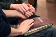 Student with hand on the Bible
