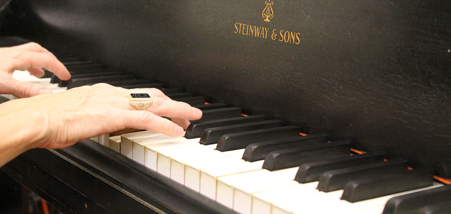 hands on piano with the woods ring