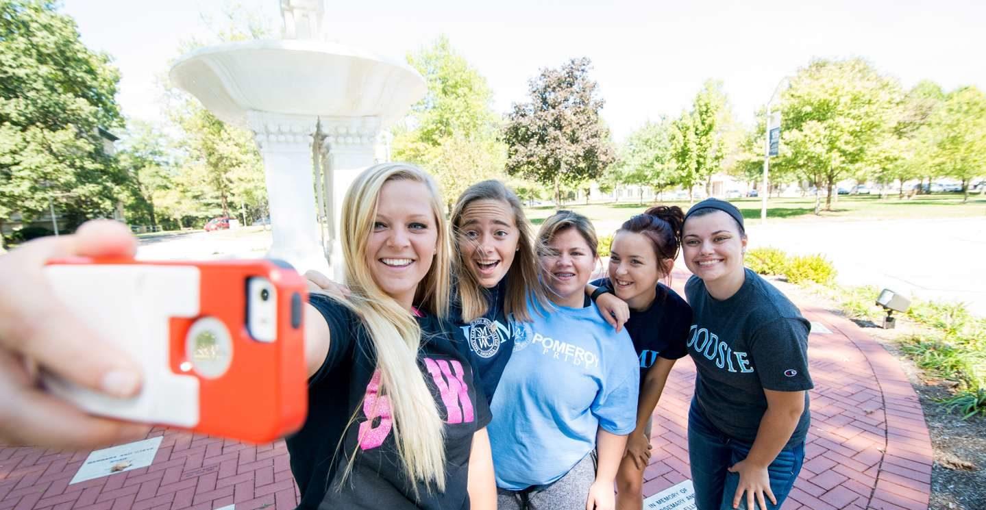 Five young women taking a selfie by fountain.