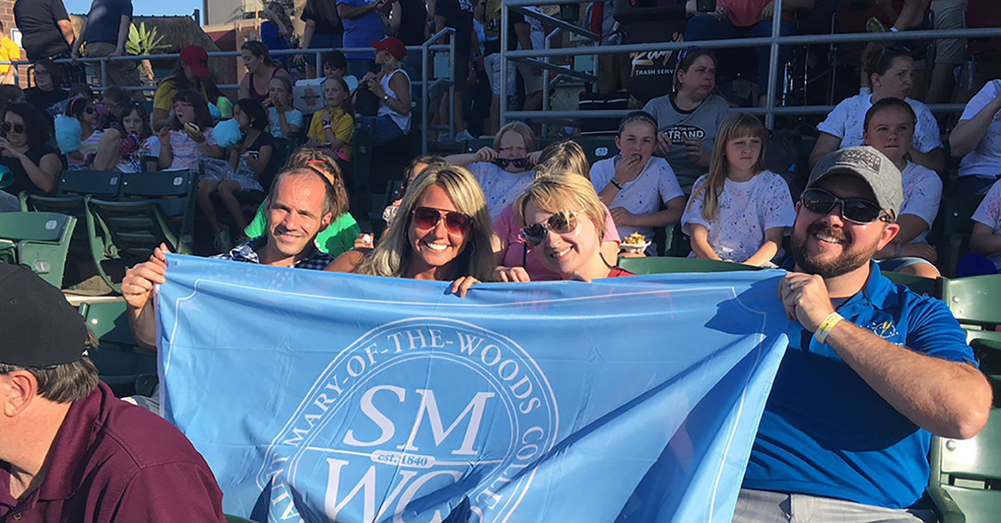 Alums holding a SMWC flag