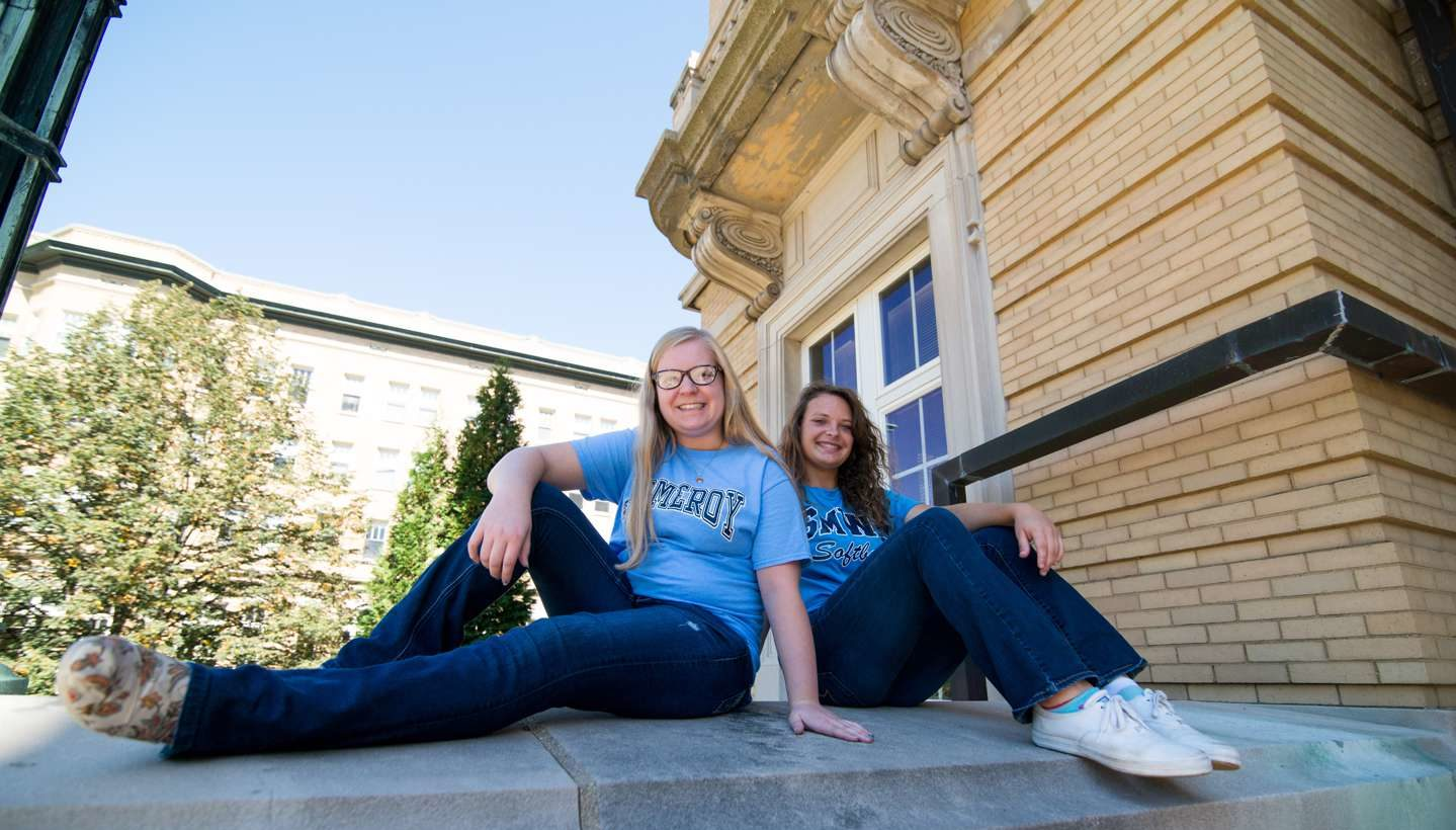 Two students sitting on steps of Le Fer Hall
