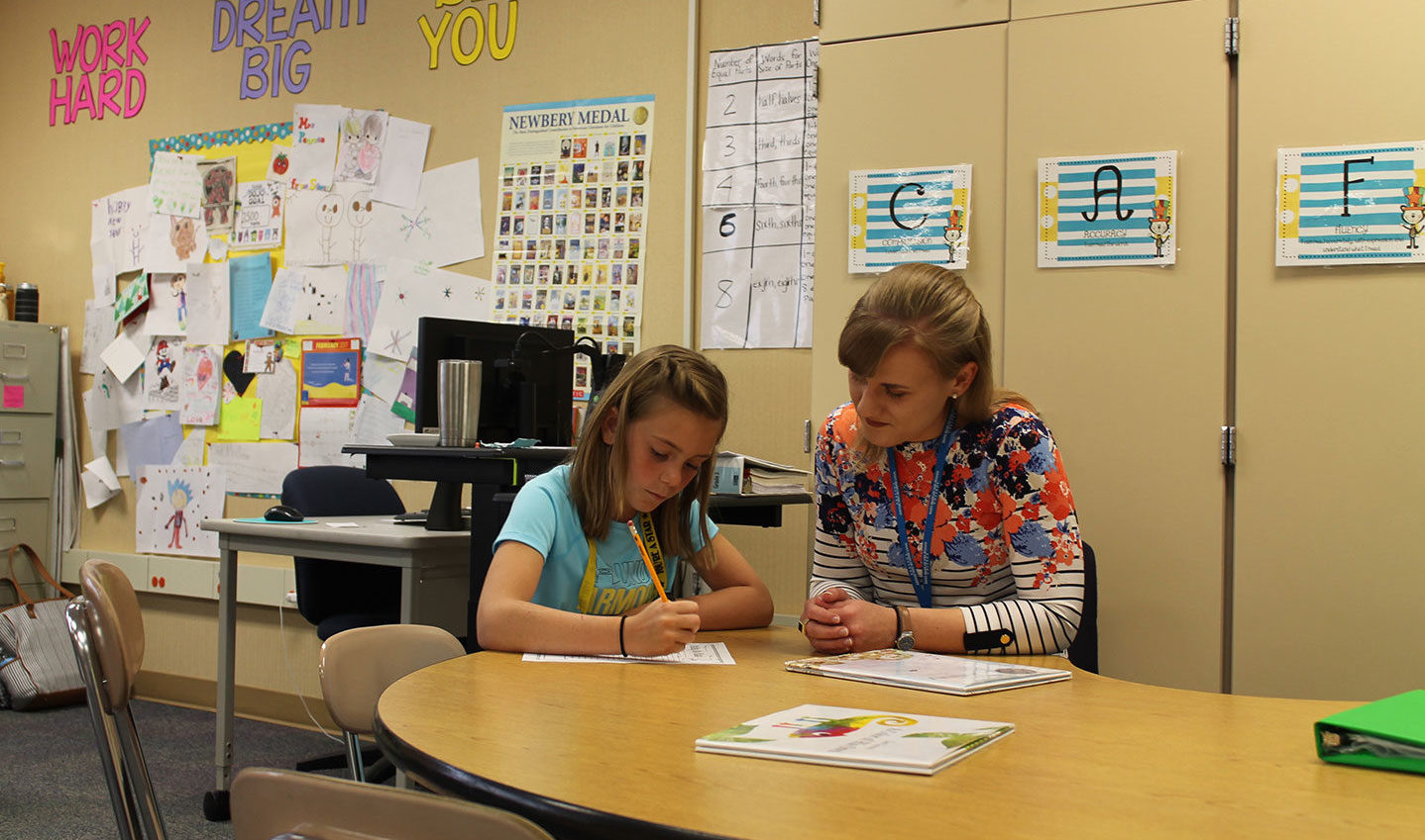 SMWC student in an elementary classroom helping a student
