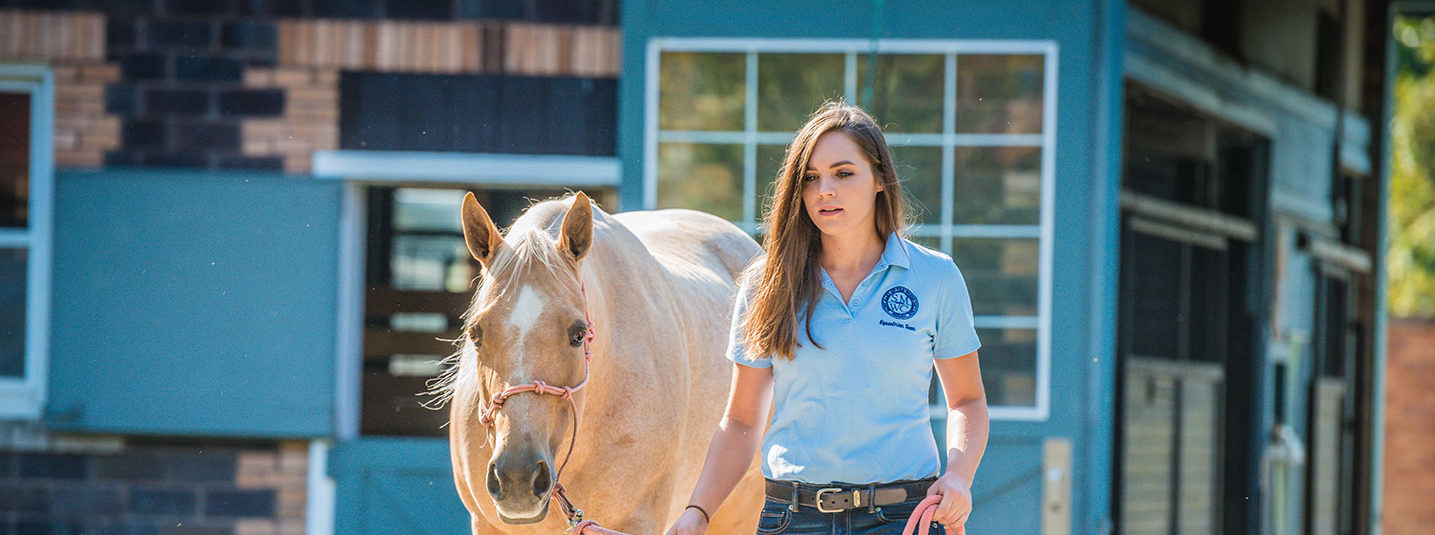 Student walking with horse outside of the barn
