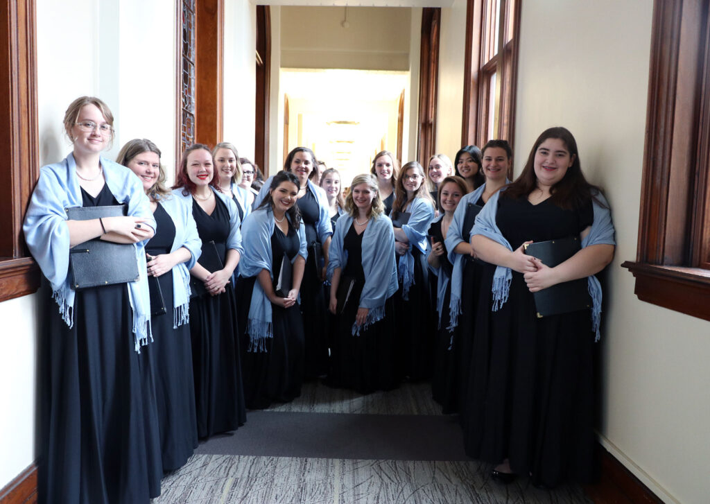 Choir students smile for a group picture before a concert