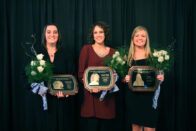 Erin, Stephanie and Jamie stand together holding their plaques at the Hall of Fame Banquet