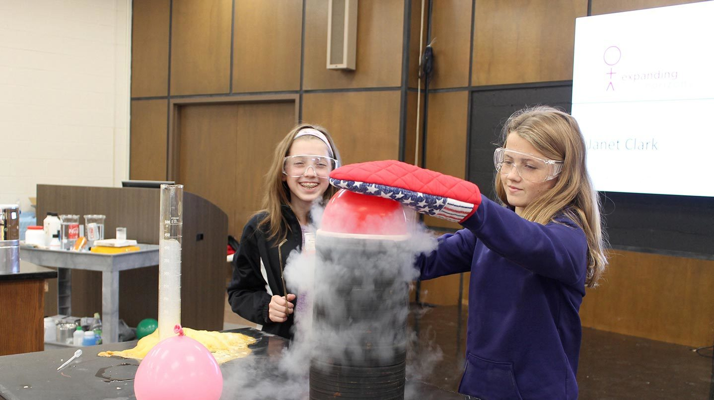 Two students freeze a balloon during a science experiment at EYH 2017