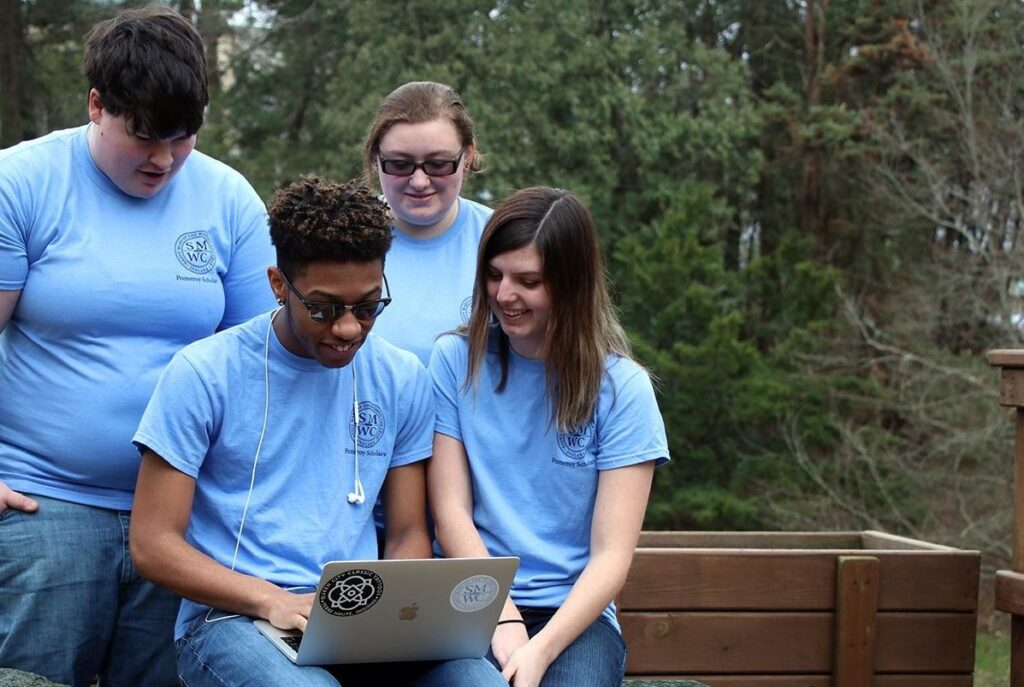 Group of Pomeroy Scholars looking at laptop
