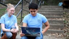 Two Pomeroy Scholars sitting on stairsteps looking at laptop