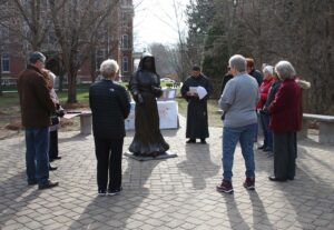 Group standing in a circle around the St. Mother Theodore Guerin statue