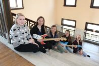 Group of music therapy students sitting on the conservatory stairs holding the custom-built guitars