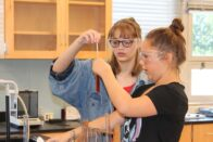 Two campers look in astonishment at beaker of colored chemicals