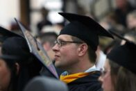 Graduates sit watching the commencement ceremony