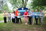 The project donors and sponsor stand in front of the Lake Le Fer sign holding a ribbon