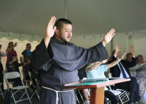 Friar Mario stands with his hands lifted up in a blessing over the lake