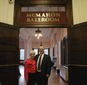 Anita and Michael McMahon stand in the doorway of ballroom.