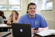 Austin Sievers sitting in classroom smiling, with books and laptop open