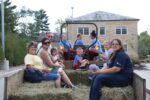 A group of families enjoying a hay ride during SMWC 2017 homecoming.