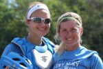 Two SMWC softball players smile for a photo at the 2017 homecoming game.