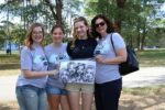 A group of students stand with SMWC alumni holding a group caricature.