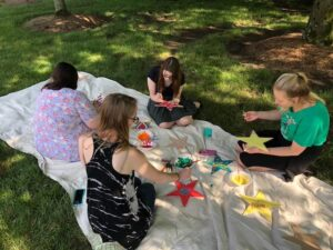 Group of MAMT students sit on a blanket painting stars.