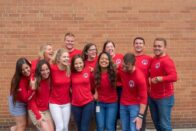 The group of interns laugh while standing for a group picture.