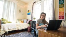 Student using laptop at their desk sitting in a dorm room