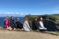 Group of SMWC choir students sitting facing the Cliffs of Moher