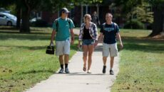 Group of three students walking up the path toward the library