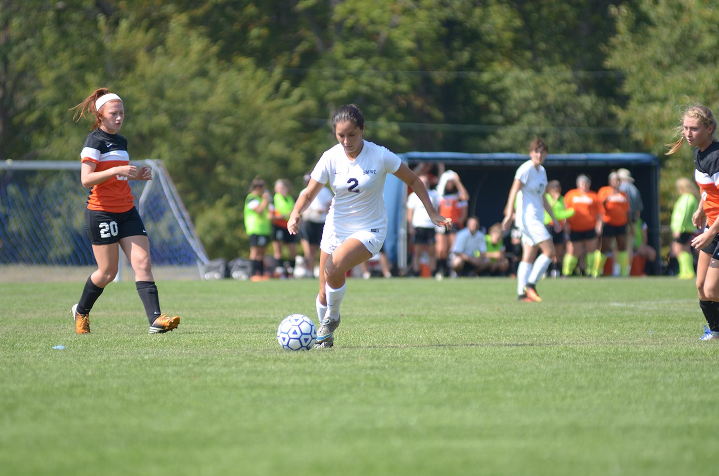 SMWC Women's Soccer player facing off with an opponent during a game