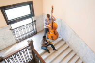 Students playing a trumpet and bass on the steps of the Conservatory