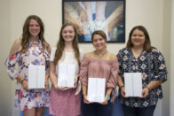 The SMTG scholarship recipients holding their tablets.