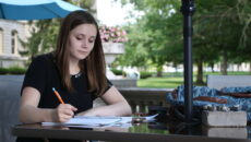 Student sits at a table outside making notes on a paper.