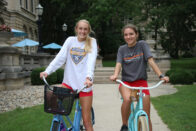 Two students sitting on bikes at the path in front of Guerin Hall