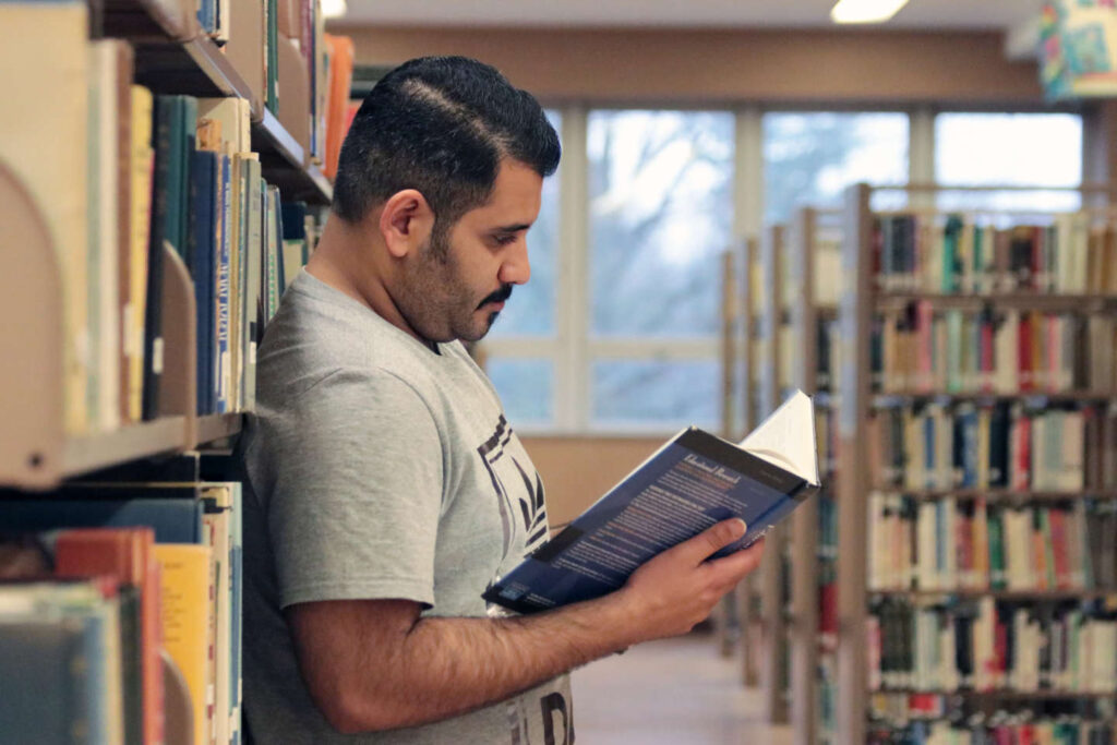 Student reading book standing in the library stacks