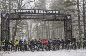 The Griffin Bike Park entrance with riders standing in the snow underneath
