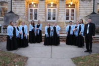 Group photo of the Madrigals on the front porch of the Conservatory of Music.