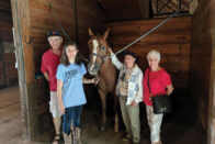 The Harmans and their granddaughter stand with a horse in the SMWC stables
