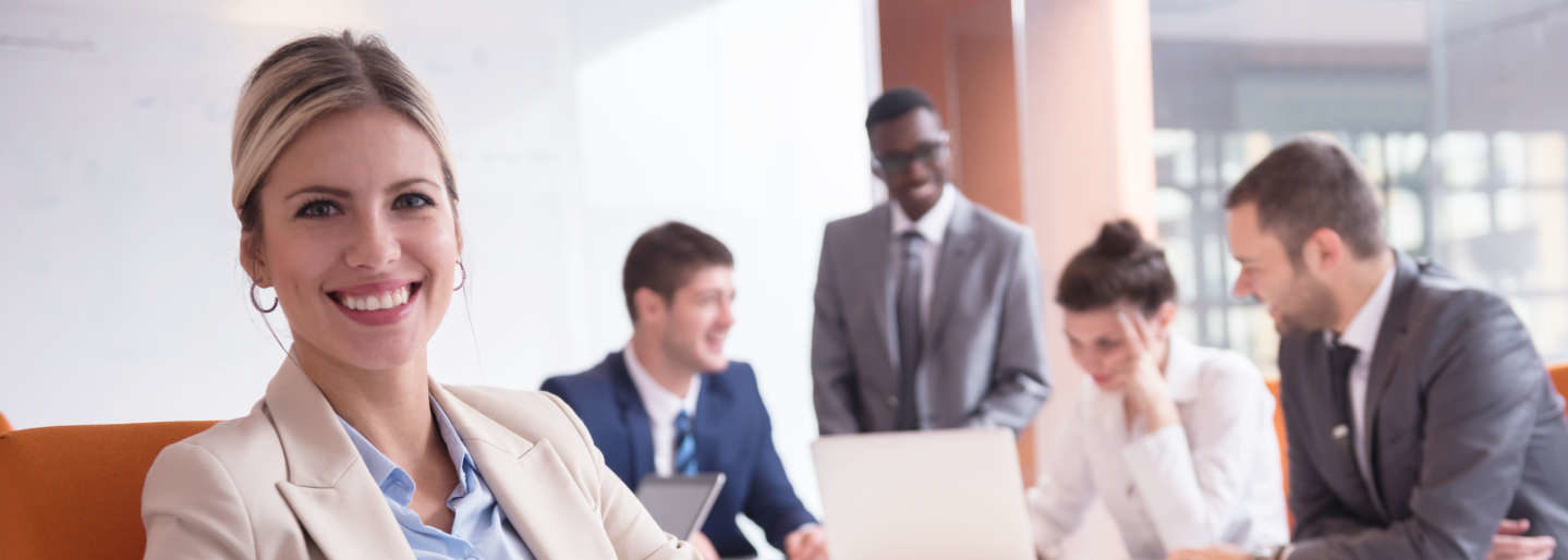 Smiling woman turned away from a group of professionals in meeting.