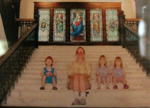 Old photo of Simmons with her triplets sitting on the main stairs of Le Fer Hall